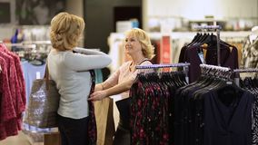 Woman selecting apparel while shopping for clothes stock video