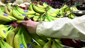 Woman selecting banana in grocery store stock video footage
