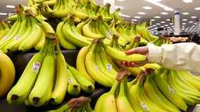 Woman selecting banana inside Walmart store stock video footage