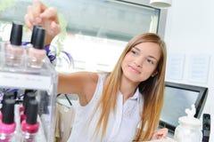 Woman selecting bottle nail polish stock photography