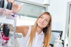Woman selecting bottle nail polish stock photo
