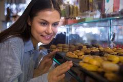 Woman selecting chocolates. Young  female customer selecting fine chocolates and confectionery at cafe display Stock Photo