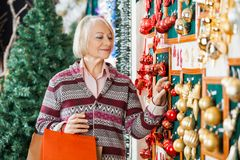 Woman Selecting Christmas Ornaments At Store Royalty Free Stock Image