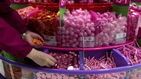 Woman selecting coin chocolate inside Party store stock video footage