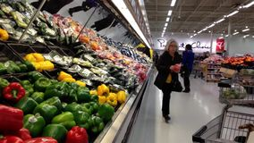 Woman selecting color peppers in grocery store stock footage
