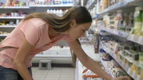 Woman selecting dairy products in fridge at grocery department of shopping mall
