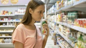 Woman selecting dairy products in fridge at grocery department of shopping mall stock image