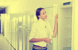 Woman selecting domestic refrigerator Royalty Free Stock Image