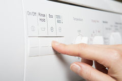 Woman Selecting Economy Program On Washing Machine To Save Energy. Woman Selecting Economy Program On Washing Machine stock image