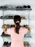 Woman selecting footwear from the shoe rack mounted on wall. Vertical image of mature woman, back towards camera, deciding which shoes to select from shoe rack royalty free stock photography
