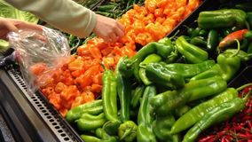 Woman selecting fresh habanero in grocery store stock video footage