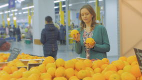 Woman selecting fresh oranges in grocery store produce department and smelling it. Young pretty girl is choosing fruits. Woman choosing orange at fruit vegetable stock footage