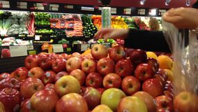 Woman selecting fresh red apples in grocery store Royalty Free Stock Photos