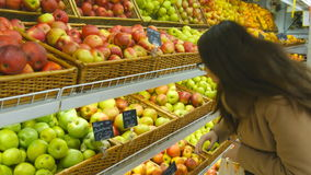 Woman selecting fresh red apples in grocery store produce department and putting it in plastic bag. Young pretty girl is stock footage
