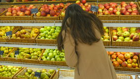 Woman selecting fresh red apples in grocery store produce department and putting it in plastic bag. Young pretty girl is stock video