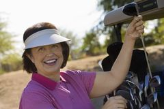 Woman selecting golf club from golf cart Stock Images