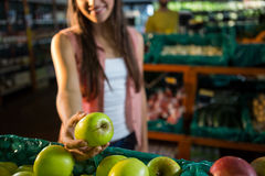 Woman selecting a green apple in organic section Stock Photos