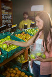 Woman selecting green apples in organic section Royalty Free Stock Photos