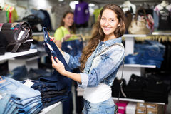 Woman selecting jeans Royalty Free Stock Photography