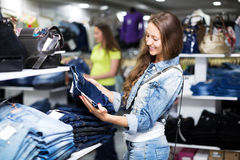 Woman selecting jeans. Beautiful young women selecting jeans in shopping center Royalty Free Stock Photos