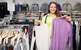 Woman selecting jersey. Smiling woman selecting jersey in the clothing store Royalty Free Stock Images
