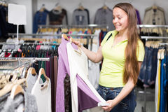 Woman selecting jersey. Smiling woman selecting jersey in clothing store Stock Photo