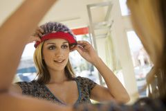 Woman Selecting Knit Cap At Store Royalty Free Stock Images