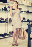 Woman selecting loafers in footgear center. Joyful young female customer selecting loafers in footgear center Royalty Free Stock Photography