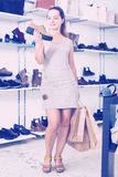 Woman selecting loafers in footgear center. Joyful young female customer selecting loafers in footgear center Royalty Free Stock Image