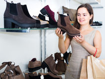 Woman selecting loafers in footgear center. Portrait of smiling young female customer selecting loafers in footgear center Royalty Free Stock Photography
