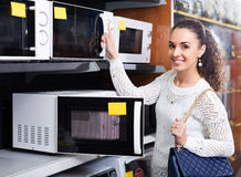 Woman selecting microwave oven Royalty Free Stock Photography