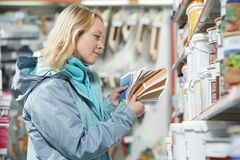 Woman selecting paint at hardware store. Young woman choosing paint using color samples during hardware shopping in home improvement store supermarket Stock Image