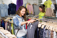 Woman selecting pants. Young women selecting pants in shopping center Stock Photo