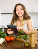 Woman selecting recipe with vegetables Stock Photography