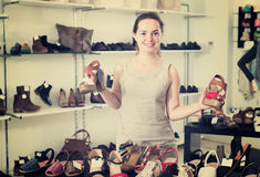 Woman selecting sandals in footgear center. Portrait of joyful young female customer selecting sandals with heels in footgear center Royalty Free Stock Image