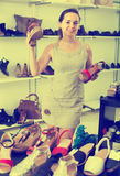 Woman selecting sandals in footgear center. Portrait of joyful young woman selecting sandals with heels in footgear center Stock Photo