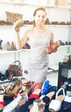 Woman selecting sandals in footgear center. Portrait of joyful young woman selecting sandals with heels in footgear center Royalty Free Stock Photos