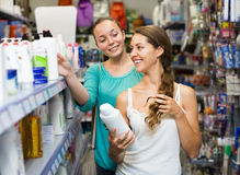 Woman selecting shampoo in store Royalty Free Stock Image