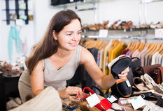 Woman selecting shoes in footgear center. Portrait of joyful young female customer selecting summer  shoes in footgear center Royalty Free Stock Photography