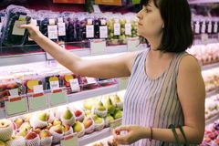 Woman selecting some grapes at the supermarket Stock Photos