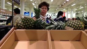 Woman selecting sweet pineapple in grocery store stock video