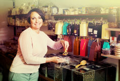 Woman selecting tea in store. Cheerful female customer selecting various tea kinds in the store with ecological goods Royalty Free Stock Image