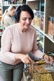 Woman selecting tea in store. Positive female customer selecting various tea kinds in the store with ecological goods Royalty Free Stock Photo