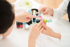 Woman selects color shellac nail polish. Top view of asian chinese women selects manicure color shellac nail polish. Nail technician shows the color palette of Royalty Free Stock Image