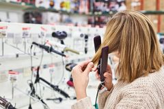 Woman selects electric straightening irons hair in shop. Woman customer selects electric straightening irons, straighteners, or flat irons hair in the store stock image