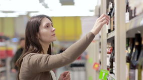 Woman selects the wine on the shelves in the store stock video