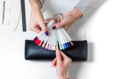 Woman selects yellow color shellac for nail stock photos