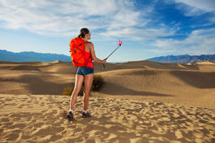 Woman with selfie stick take image in Death valley Stock Photography