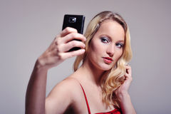 Woman selfortrait. Beautiful long haired blonde woman posing for a self portrait in a studio setting. With one hand holding her phone, with the other hand doing Royalty Free Stock Photography