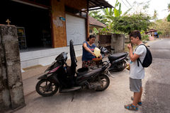 Woman sell benzine in plastic bottle. BALI, NUSA PENIDA ISLAND, INDONESIA - JULY 28.2015: Balinese woman pour fuel into motorbike. Street fuel petrol station in Stock Photo